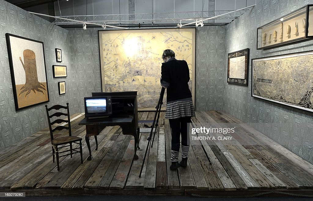 A woman takes photos of the work of artist Duke Riley during the press preview at the 2013 Armory Show, one of the world's top art events featuring the most influential artworks of the 20th and 21st centuries, at Pier 92 and 94 in New York March 6, 2013. The Armory Show Centennial Edition kicks off Armory Arts Week .