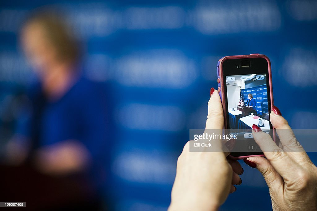 A woman takes photos with her iPhone as Stephanie Schriock, president of Emily's List, holds a news conference at the National Press Club on Monday, Jan. 7, 2013, to speak about the strategy that swept new Democratic women lawmakers into Congress.
