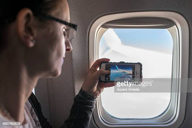 Woman takes pic from plane window, above clouds