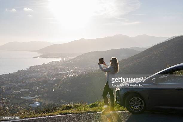 Woman takes pic with digital tablet by car at view