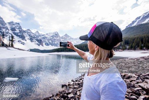 Woman takes picture across still frozen mtn lake