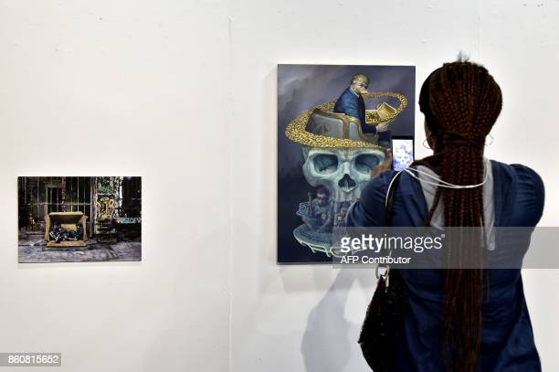A woman takes picture of a new artwork by Baliborn grafitti artist WD entitled 'Age of abundance' which features US President Donald Trump during the...
