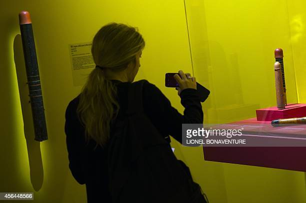 A woman takes picture of an ancient dildos displayed as she visits the exhibition The KamaSutra spirituality and erotism in Indian art at the Paris'...