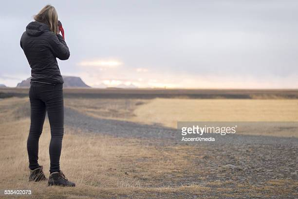 Woman takes picture of road in volcanic landscape