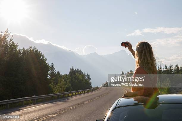 Woman takes picture through car's roof, of sunrise