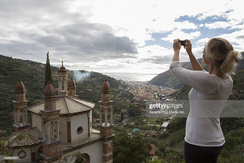 Woman takes picture with cell phone, cathedral : Stock Photo