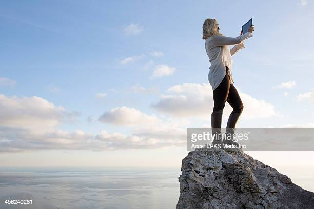 Woman takes picture with digital tablet, above sea