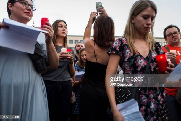 A woman takes picture with her mobile phone as protesters take part in a candlelit vigil at the site of the Polish embassy in Berlin on July 21 2017...
