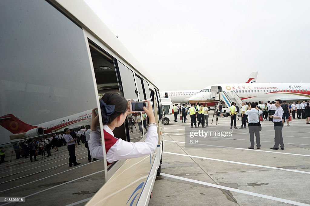 A woman takes pictures as an ARJ21-700, China's first domestically produced regional jet, arrives at Shanghai Hongqiao Airport after making its first flight from Chengdu to Shanghai on June 28, 2016. China's homegrown regional jet made its first commercial flight on June 28, Chengdu Airlines said, after months of delays raised questions about the country's ambitious plans for domestically produced planes. / AFP / STR / China OUT