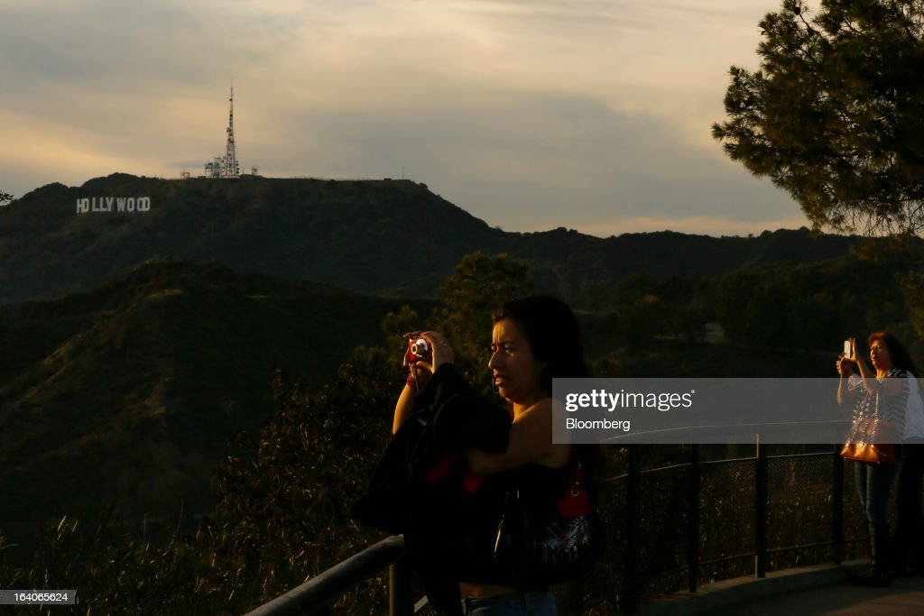 A woman takes pictures at sunset from the Griffith Park Observatory, with the Hollywood Sign in the background in Los Angeles, California, U.S., on Thursday, March 14, 2013. California should start a state-run bank to finance economic development that's less polluting and more environmentally friendly, financed by auctions of greenhouse-gas carbon credits, Lieutenant Governor Gavin Newsom said. Photographer: Patrick T. Fallon/Bloomberg via Getty Images