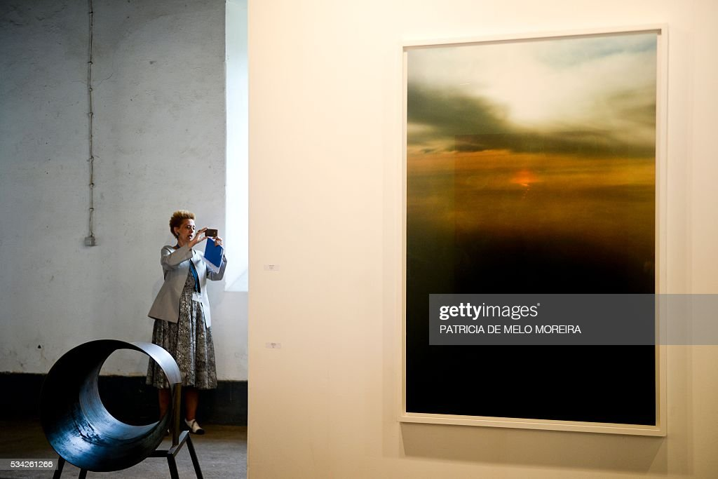 A woman takes pictures close to the Spanish gallery 'Juana De Aizpuru' stand during the ARCO Lisbon Contemporary Art Fair in Lisbon on May 25, 2016. ARCO will be open to the public from May 26 to 29. / AFP / PATRICIA