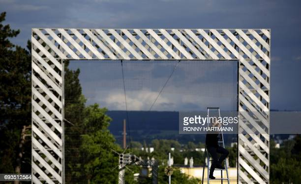 A woman takes pictures infront of the 'Rahmenbau' by artist group HausRuckerCo during the Documenta 14 art exhibition in Kassel on June 7 2017...