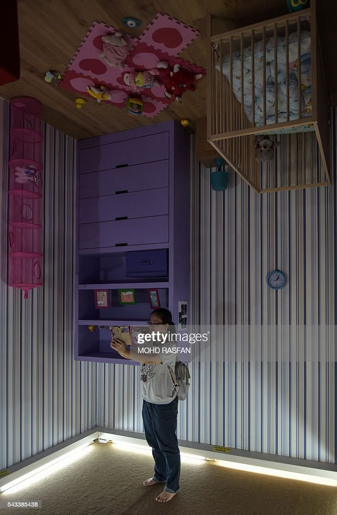 A woman takes pictures inside the Kuala Lumpur Upside Down House at KL Tower in Kuala Lumpur on June 28, 2016. Kuala Lumpur Upside Down House is a two-storey house and is the latest attraction for tourists arriving to the Malaysian capital where everything inside such as the furniture are placed in an upside down position. / AFP / MOHD