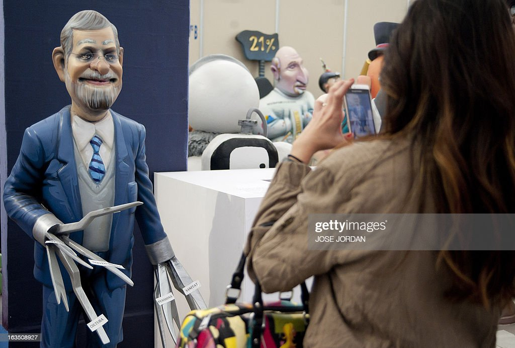 A woman takes pictures of a Falla, a gigantic sculpted structure of cardboard and wood which humorously portrays relevant current events and personalities, caricaturing Spain's Prime Minister Mariano Rajoy during an exhibition before preparations for the Fallas Festival, in Valencia on March 11, 2013. The Fallas will be burned in the streets of Valencia on March 19, 2013, as a tribute to St. Joseph, patron saint of the carpenters' guild.