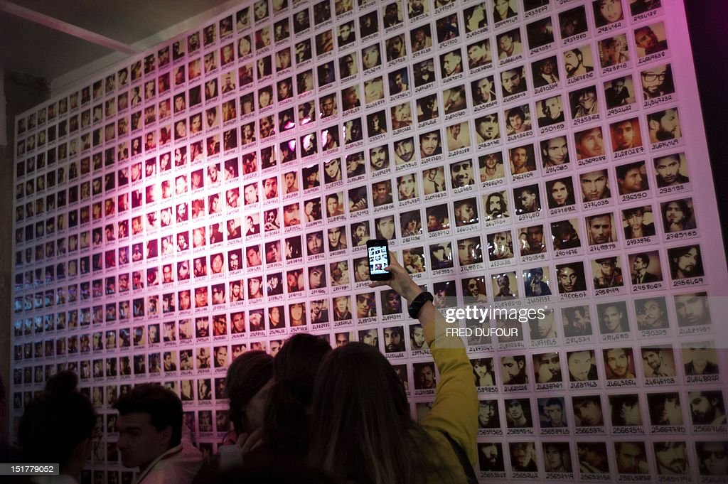 A woman takes pictures of a wall on which appear portraits of men, on September 11, 2012 in Paris, on the opening day of a store of the online dating site 'AdopteUnMec.com' (AdoptAGuy.com), where women can choose and also date men, standing in boxes like toys, according to their profiles and taste. This travelling store will open ten days in Paris, before going to Brussels, Lausanne, Toulouse and Lyon and then going back to Paris.