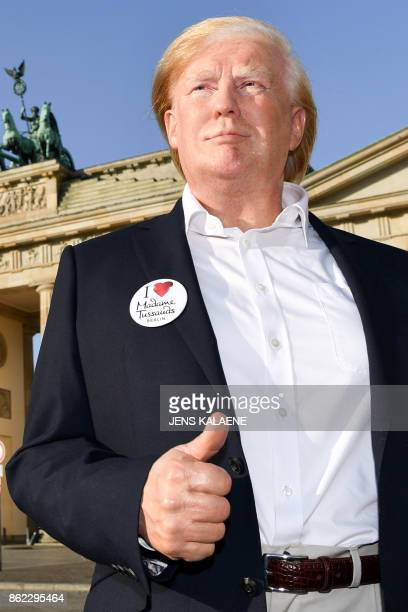 A woman takes pictures of Madame Tussauds museum's wax figure of US President being displayed on October 17 2017 at the Brandenburg Gate in Berlin...