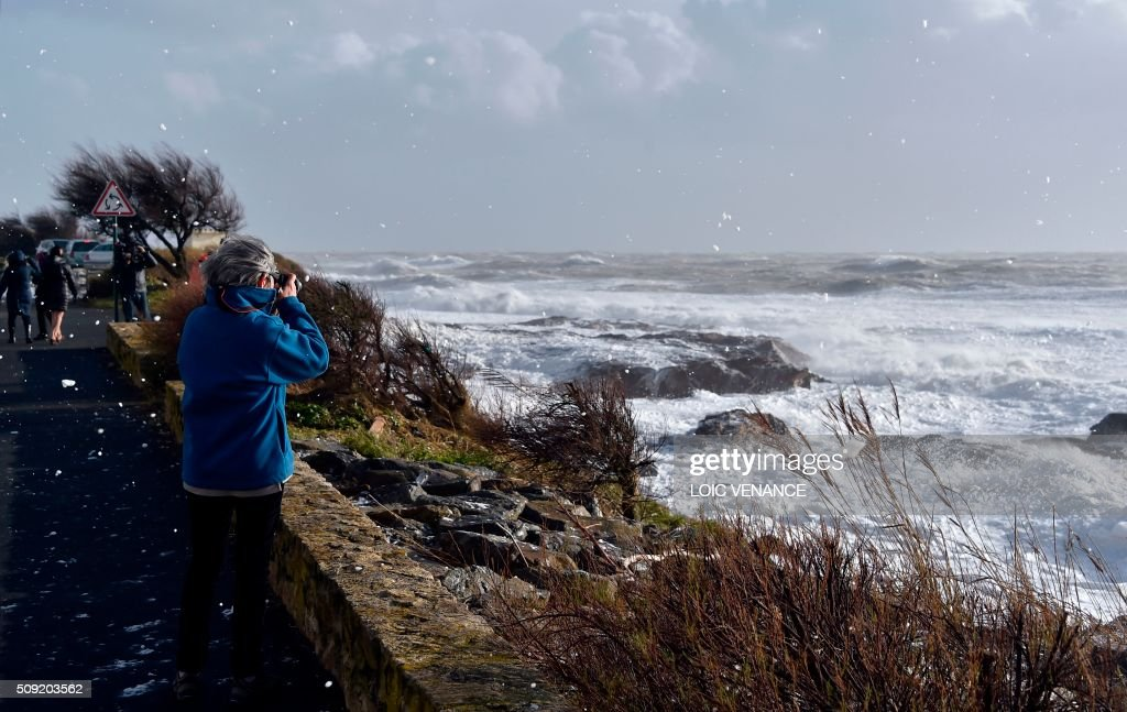 A woman takes pictures of the sea in Les Sables-d'Olonne, western France, on February 9, 2016. High winds buffeted northwestern Europe on February 8, leaving one woman in France in a coma after she was hit by an advertising hoarding. Electricity was cut to 5,000 homes in northern France. / AFP / LOIC VENANCE
