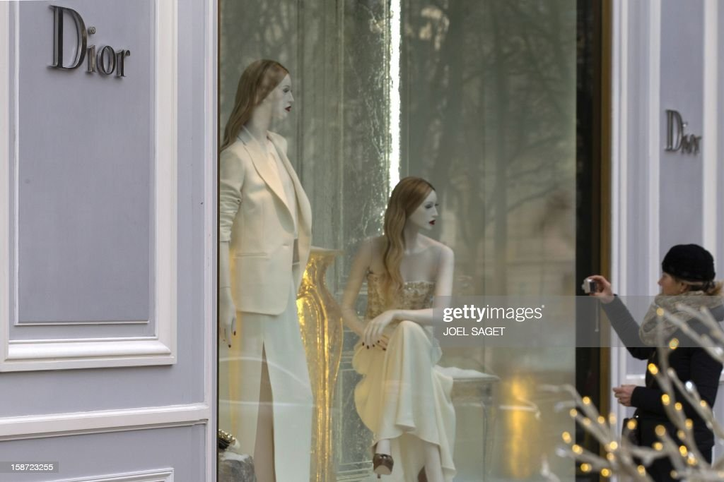 A woman takes pictures of the shop window of a Dior store, on December 26, 2012 in Paris. AFP PHOTO / JOEL SAGET