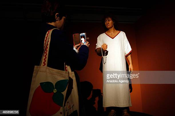 Woman takes pictures of the wax figure 'The Young Phoenician Man of Carthage' is seen during the opening of a special exhibition at the American...