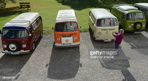 A woman takes pictures of vintage Volkswagen buses during an autumn rally of socalled 'Bulli' enthousiasts in front of the abbey Schaeftlarn near...