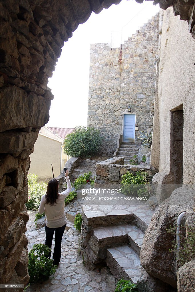A woman takes pictures on September 19, 2013 in San Antonino village, on the French Mediterranean island of Corsica. San Antonino is listed as one of the most beautiful villages of France. AFP PHOTO / PASCAL POCHARD-CASABIANCA
