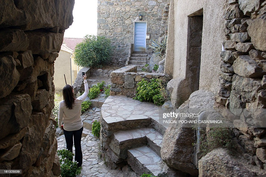 A woman takes pictures on September 19, 2013 in San Antonino village, on the French Mediterranean island of Corsica. San Antonino is listed as one of the most beautiful villages of France.