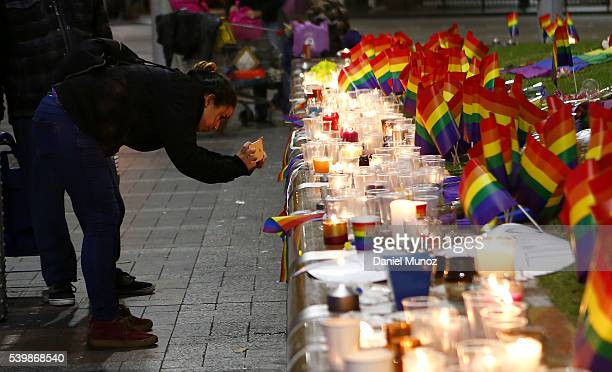 A woman takes pictures with her phone during a candlelight vigil for the victims of the Pulse Nightclub shooting in Orlando Florida at Oxford St on...