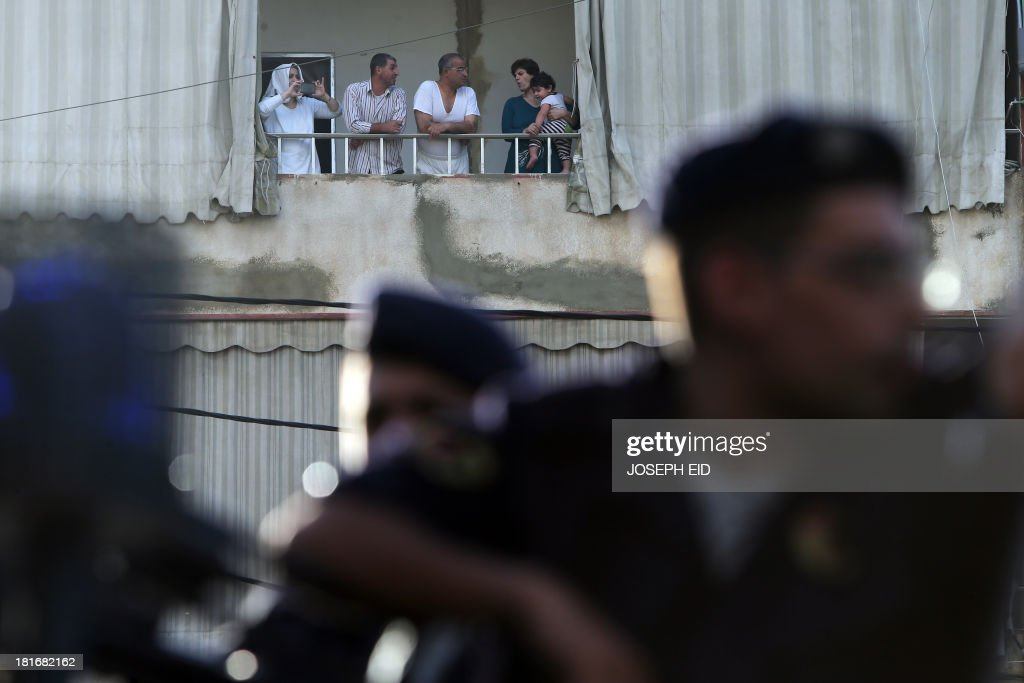 A woman takes pictures with her phone from a balcony as Lebanese soldiers prepare to install a checkpoint in the southern suburb of the capital Beirut on September 23, 2013. Lebanese troops are to take over security at checkpoints set up by the Hezbollah movement in their southern Beirut stronghold after two bombings, the interior minister told AFP.