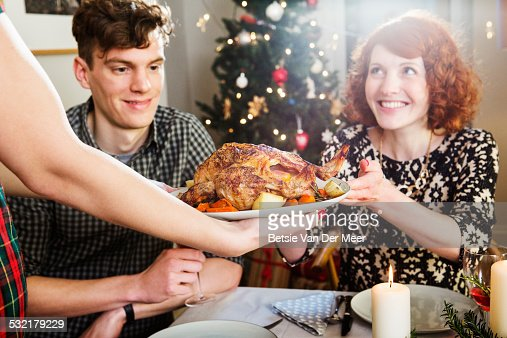Woman takes plate with turkey at Christmas dinner.