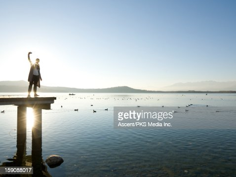 Woman takes self portrait on lake pier, sunrise : Stock Photo