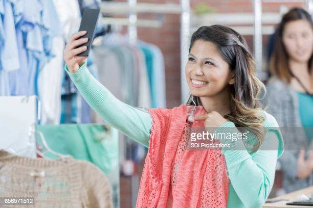 Woman takes selfie in clothing store