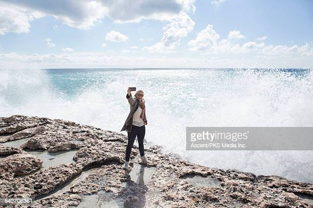 Woman takes selfie portrait above sea surf