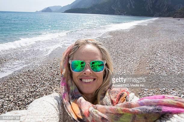 Woman takes selfie portrait on empty beach