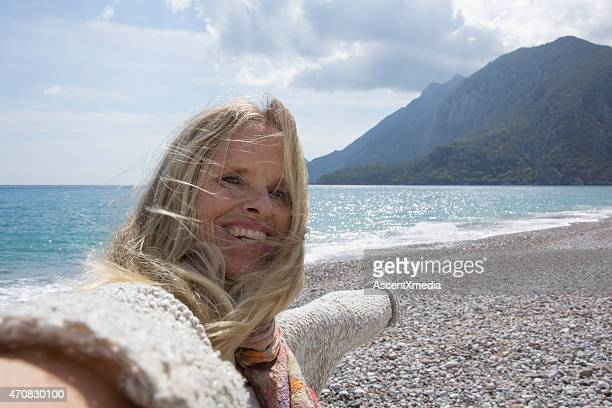 Woman takes selfie portrait on pebble beach, sea behind