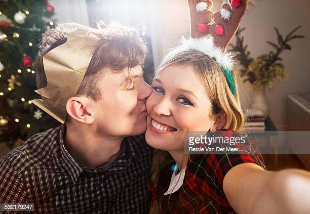 Woman takes Selfie while boyfriend kisses her.