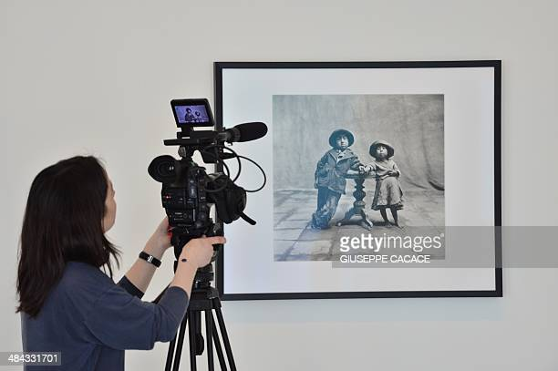 A woman takes shots of a picture by photographer Irving Penn 'Cuzco Children' as part of the exhibition 'Irving Penn Resonance' at Palazzo Grassi in...