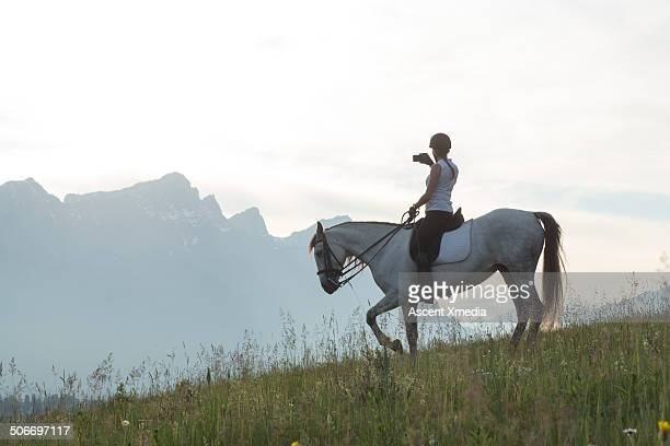 Woman takes smart phone pic from horse, mtn meadow