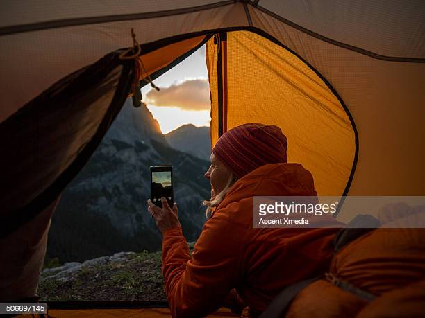 Woman takes smart phone pic of sunrise, in tent