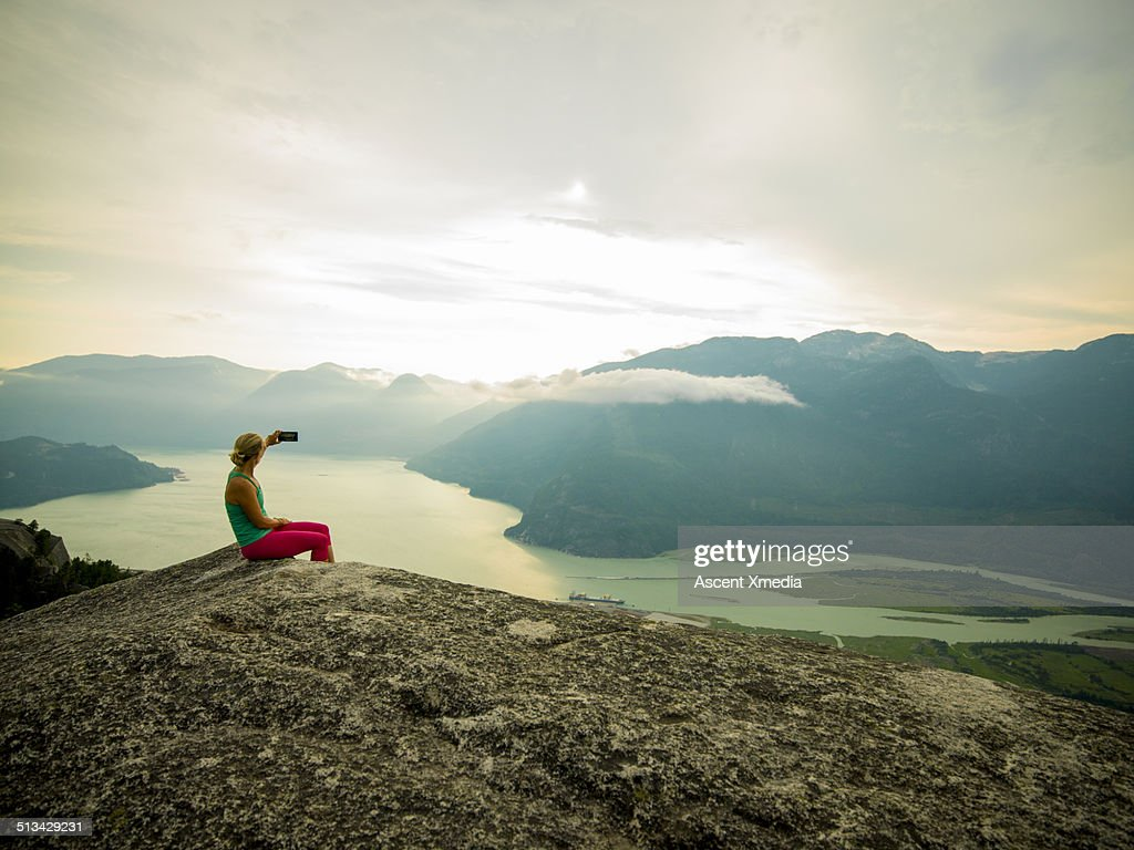 Woman takes smart phone pic on mtn summit