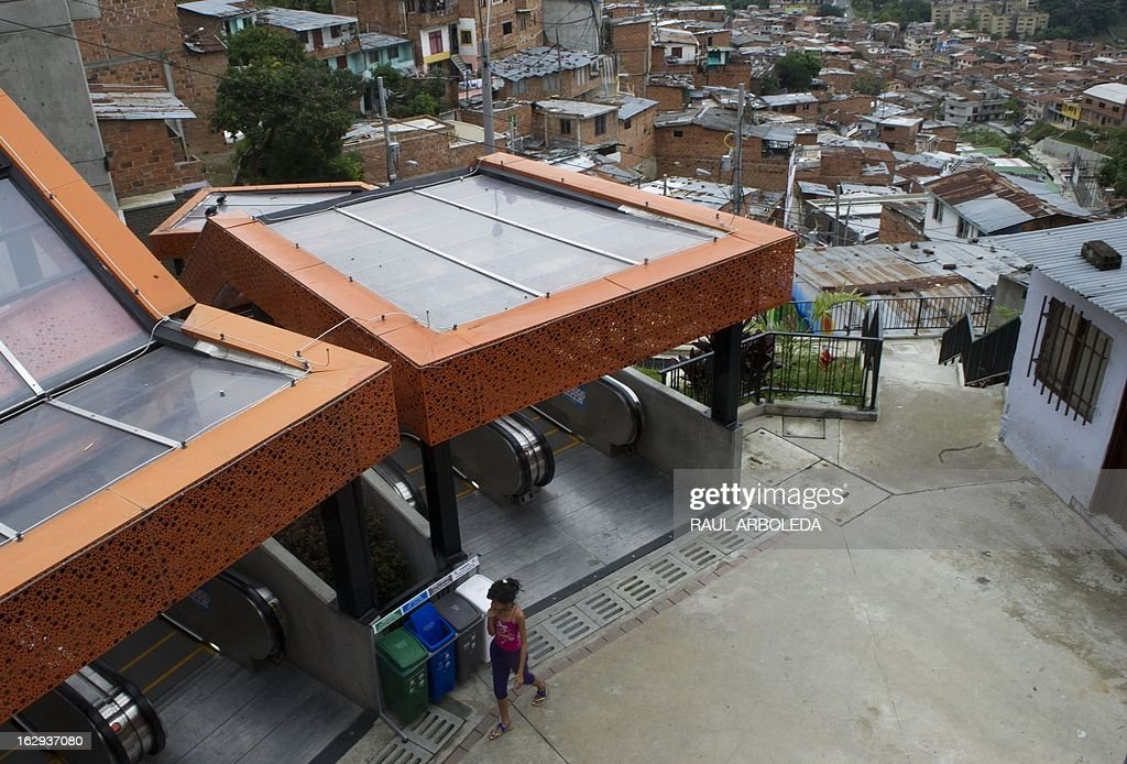 "A woman takes the escalators at Comuna 13 neighbourhood, one of the poorest and most violent areas of the northeastern Colombian city of Medellin, Antioquia department, Colombia on March 1, 2013. Medellin, which competed with New York and Tel Aviv, was chosen by popular vote through the internet, as the ""Innovative City of the Year"" during the City of the Year contest, organized by The Wall Street Journal and Citigroup. The distinction was basically made for its modern transportation system, its public library, escalators built in a shantytown and schools that have allowed the integration of society. AFP PHOTO/Raul ARBOLEDA"