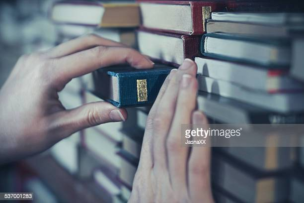Woman reaching book from shelf