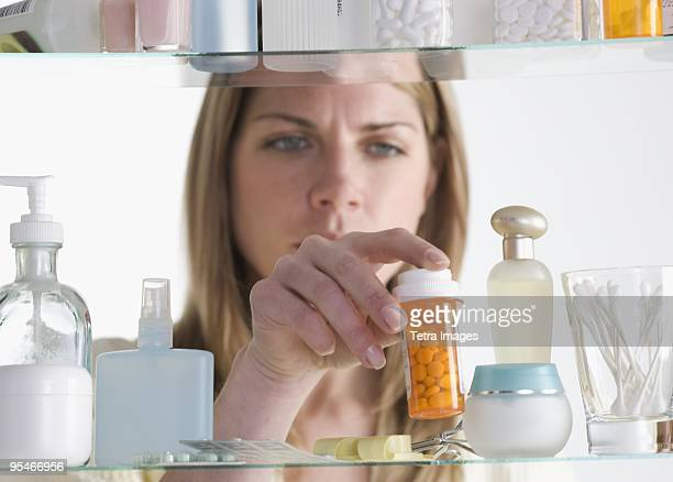 Woman taking a bottle of pills from a medicine cabinet