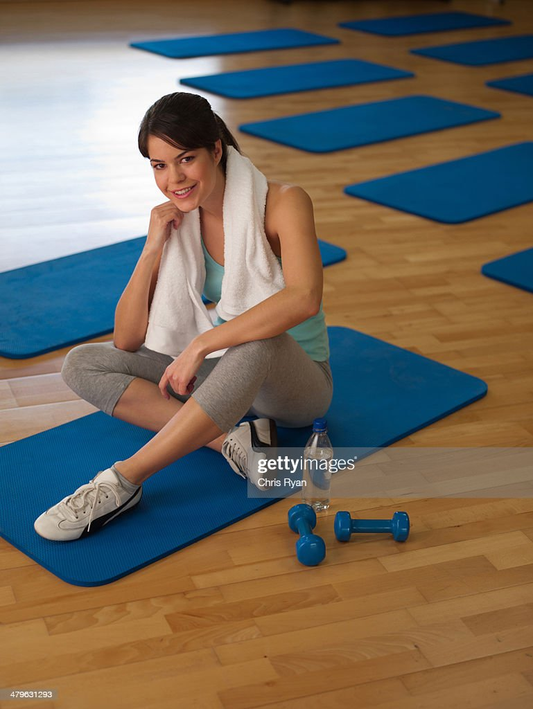 Woman taking a break from doing mat exercises in a fitness studio : Stock Photo