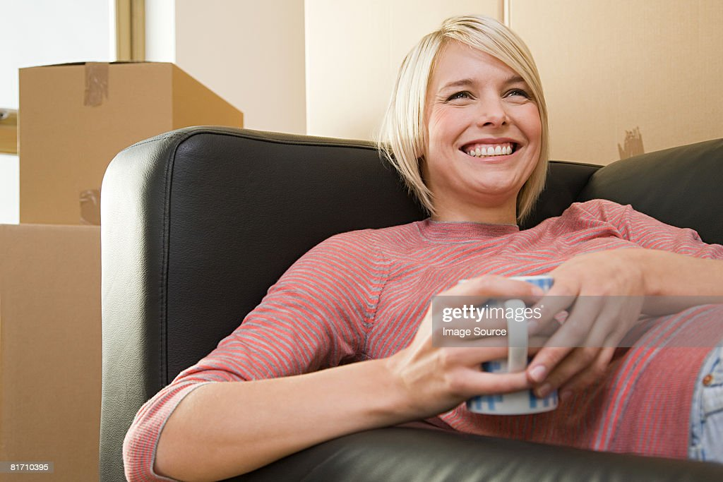 Woman taking a break from moving in : Foto de stock