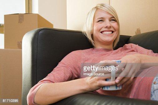Woman taking a break from moving in : Foto de stock