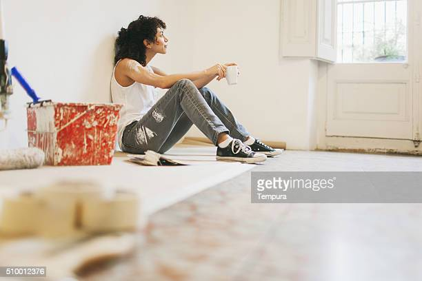 Woman taking a break while painting apartment.