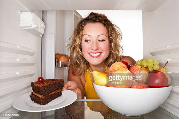 Woman taking a cake out of the fridge