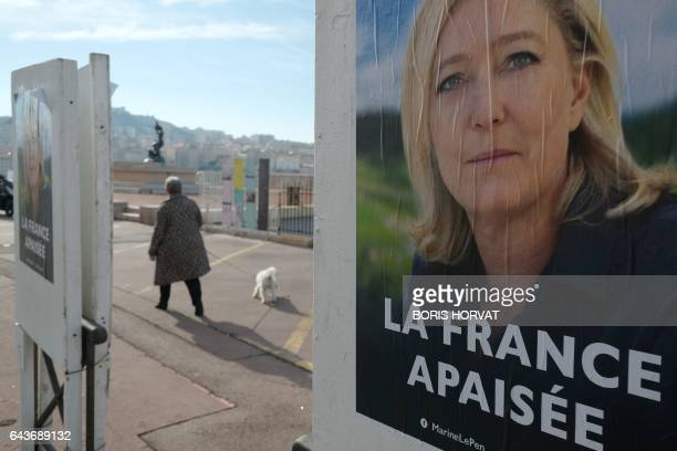 A woman taking a dog for a walk passes by a poster for French presidential election candidate for the farright Front National party Marine Le Pen in...