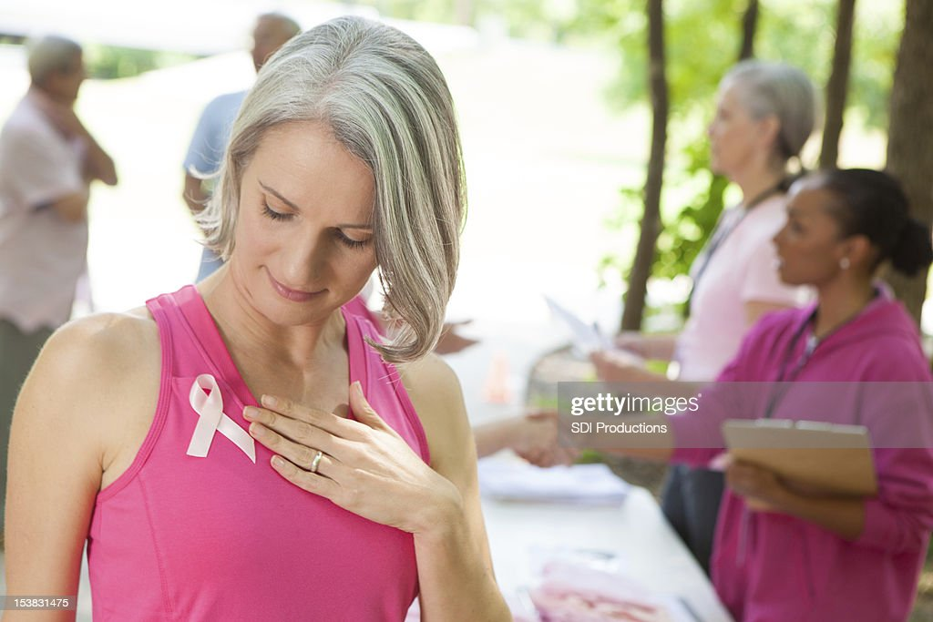 Woman looking at her ribbon before breast cancer awareness event