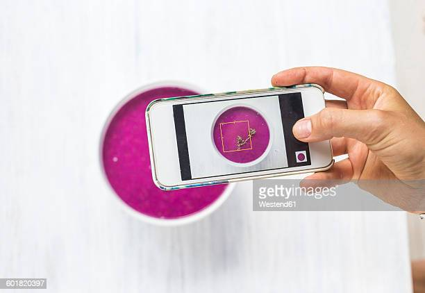 Woman taking a photo of dragon fruit smoothie with her smartphone, close-up
